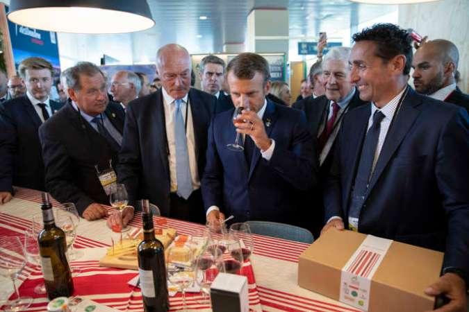 Emmanuel Macron, accompagné du président de la Nouvelle-Aquitaine, Alain Rousset (à gauche), goûtedes produits locaux, à Anglet, le 24 août.