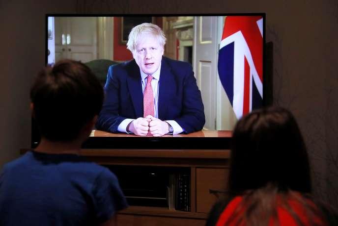 Deux enfants regardent à la télévision la conférence de presse de Boris Johnson alors que la propagation du Covid-19 se poursuit à Hertford, en Grande-Bretagne, le 23 mars 2020.