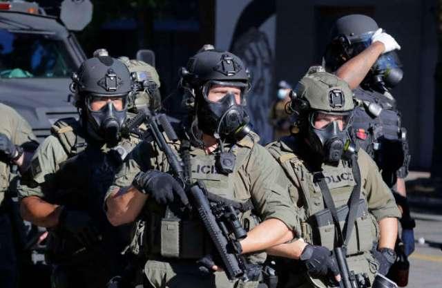 Des agents des forces de l'ordre armés lors d'un manifestation «Black Lives Matter» près du quartier général de la police de Seattle Est, à Seattle, samedi 25 juillet.