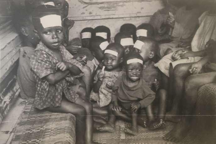 De jeunes orphelins biafrais lors de leur évacuation au Gabon par avion militaire, en octobre 1968. Sur leur front ont été collés des morceaux de sparadrap où figurent leur nom et celui de leur village d'origine.
