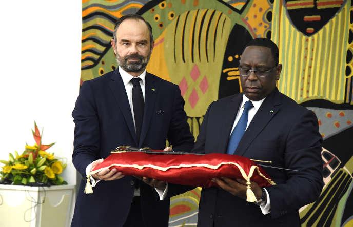 Le président du Sénégal Macky Sall (à droite) reçoit le sabre dit d'El Hadj Omar Tall des mains du premier ministre français Edouard Philippe au palais de la République à Dakar, le 17 novembre 2019.