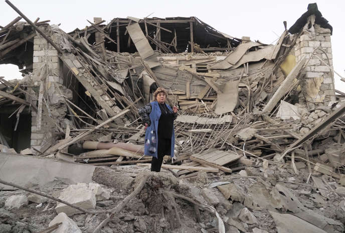A resident of Stepanakert in front of her destroyed home.