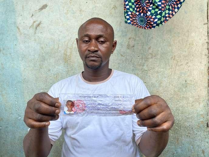 Claude Ngwane montre les papiers d'identité de sa filleRenny, 12 ans, assassinée avec six autres élèves, le 24 octobre 2020, par des hommes armés dans son école, à Kumba, dans la région anglophone du Sud-Ouest, au Cameroun.