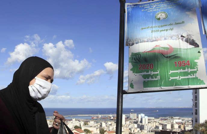 Une femme passe devant une affiche annonçant le référendum de dimanche 1er novembre en Algérie, le 27 octobre à Alger.