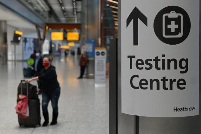 Un panneau indique un centre de test pour le Covid-19, à l'aéroport d'Heathrow à Londres, le 9 février 2021.