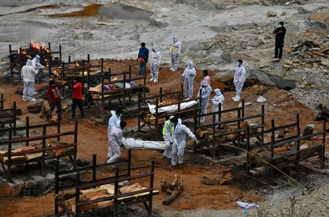 Des bénévoles s'apprêtent à brûler le corps d'une victime du Covid-19, le 2 mai 2021 à Giddenahalli, près de Bangalore.