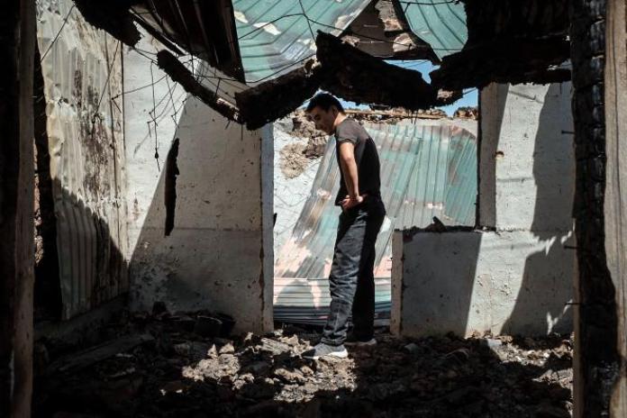 Un homme, au milieu des ruines de son commerce incendié, à Maksat, au Kirghizistan, à la frontière avec leTadjikistan, le 2 mai 2021.