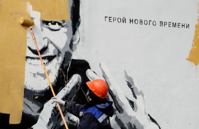 Un ouvrier repeint un portrait de l'opposant Alexeï Navalny à Saint Pétersbourg, en Russie, le 28 avril 2021. A côté du portrait, on peut lire : « Le héros d'une nouvelle époque».