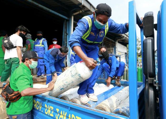 Des employés portent des bouteilles d'oxygène dans une usine à Jakarta, en Indonésie, le 6 juillet 2021.