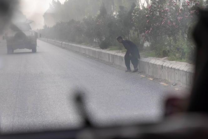 Un civil court s'abriter tandis que les forces spéciales afghanes affrontent les talibans pour secourir un officier de police capturé à un poste-frontière, dans la province de Kandahar, le 13 juillet 2021.