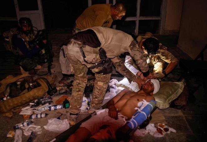 Des membres des forces spéciales afghanes s'occupent d'un soldat de l'armée nationale afghane, blessé dans des affrontements avec les talibans, dans la province de Kandahar, en Afghanistan, le 12 juillet 2021.