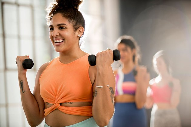 Woman lifting weights during Corepower Yoga workout class