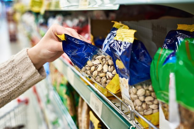 A person's hand grabbing a package of pistachios in the supermarket