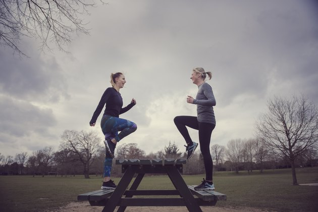 Full length side view of women doing step-ups on picnic bench