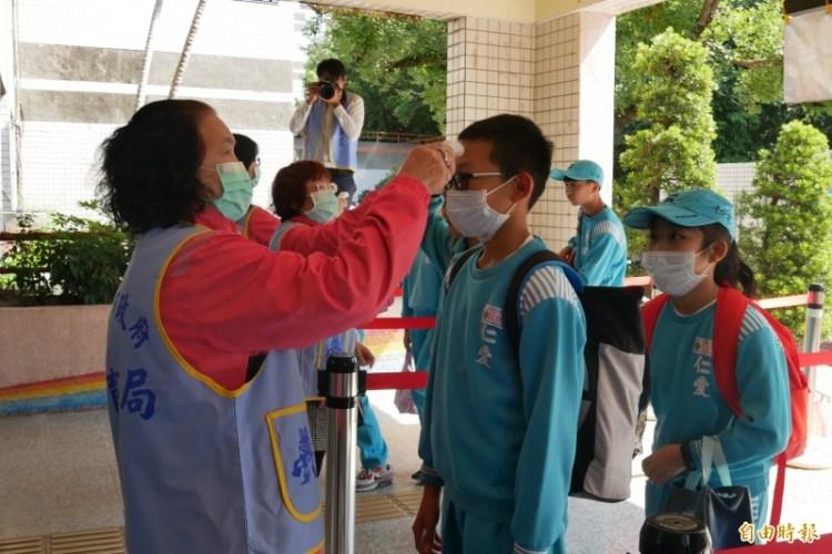 各級學校即將開課,教肓部訂出停課標準。圖為各學校配合防疫,替上學的學生們量測體溫。(記者邱書昱攝)