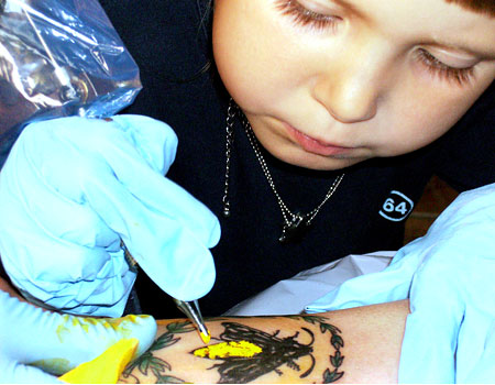 Tattoo girl Emilie Darrigade puts the finishing touches to her dad's tattoo