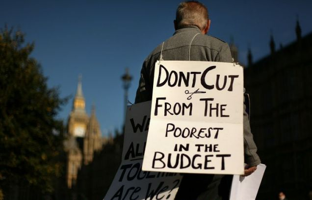 A protestor wears a placard near Parliament as part of the backlash against George Osborne's cuts (Picture: Getty)