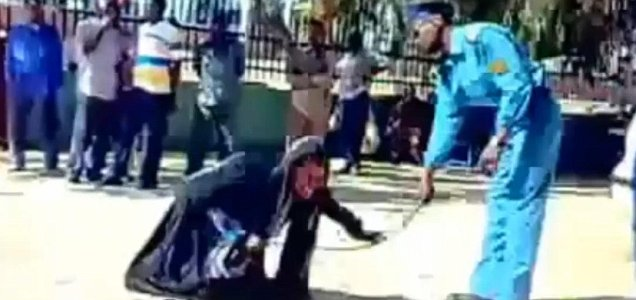 A policeman gives a woman a public whipping for wearing trousers underneath her Islamic clothing in Sudan (YouTube)