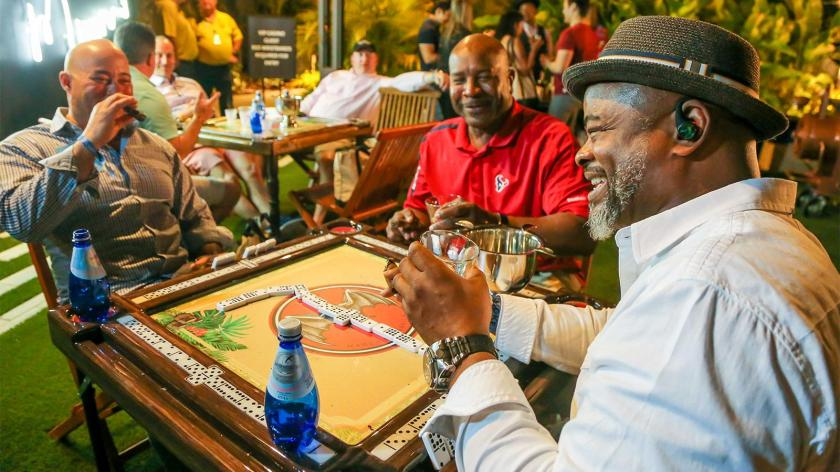 Rico Cortez, left, Norman Bell and Clarence Watkins play dominoes while smoking cigars and sipping their drinks.