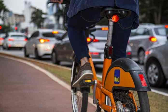 Foto mostra uma bike da Tembici, em parceria com o Itaú, em uma ciclovida da cudade; uma pessoa está pedalando a bicicleta