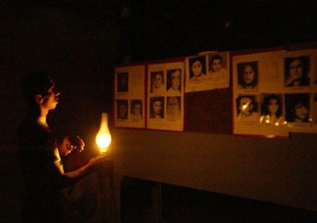 Un garçon irakien regarde des photos de victimes d'un raid aérien étatsunien en 1991 qui a tué 450 hommes, femmes et enfants abrités dans un refuge d'Al-Ameriyah à Bagdad. Irak, le 17 juillet 2003 (AFP)