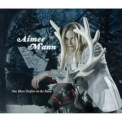 "Cover of Aimee Mann's album ""One More Drifter in the Snow,"" which depicts a white woman sitting on a plastic reindeer in an outdoor environment."
