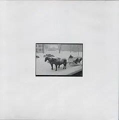 Cover of Bright Eyes' holiday album, which shows a black-and-white photograph of two horses in the snow, with a sleigh behind them. The photograph is placed on an off-white background.