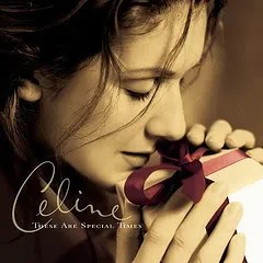 "Cover of Celine Dion's album ""These Are Special Times,"" which features a sepia-toned portrait of Dion holding a small gift up to her face. She appears to be inhaling it."