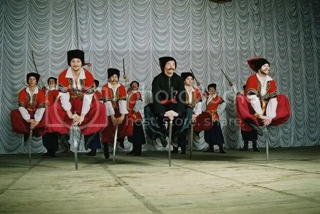 cossack dancers doing uncomfortable folded-leg leaping close to pointy swords