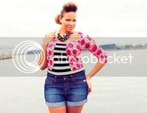 Eine schwarze Frau mit sehr weiblichen Kurven und einer großen Elvis-Tolle in Jeans-Hotpants, schwarz-weiß gestreiftem Top und einer kurzärmligen weißen Jacke mit rosa Punkten vor der See mit einem blauen Schiff am Horizont
