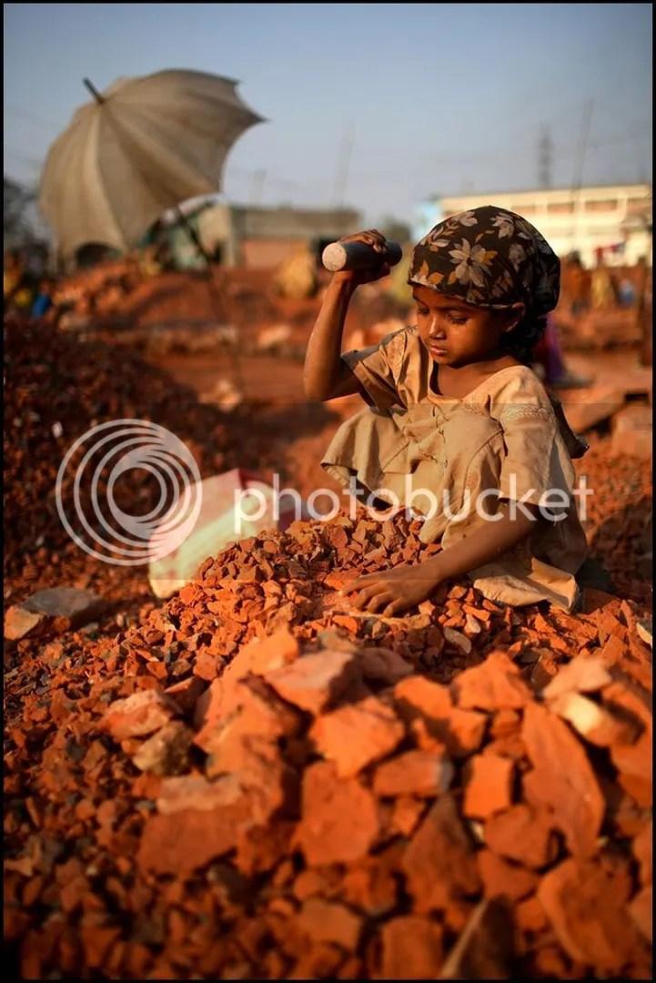 Seorang anak perempuan sedang bekerja di pabrik penghancur batu bata.