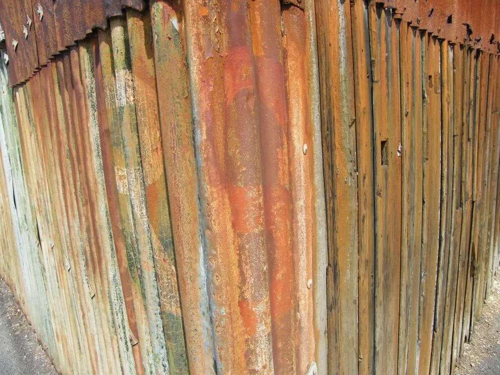 A corrugated building, rusted in various colours