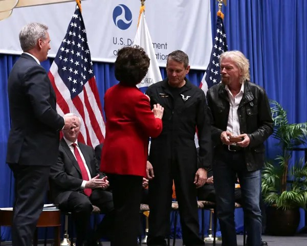 U.S. Transportation Secretary Elaine L. Chao pins a Commercial Astronaut Wing to Mark 'Forger' Stucky's Virgin Galactic uniform as Sir Richard Branson watches...on February 7, 2019.