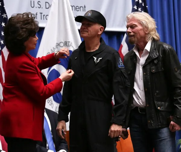 U.S. Transportation Secretary Elaine L. Chao is about to pin a Commercial Astronaut Wing to CJ Sturckow's Virgin Galactic uniform as Sir Richard Branson watches...on February 7, 2019.