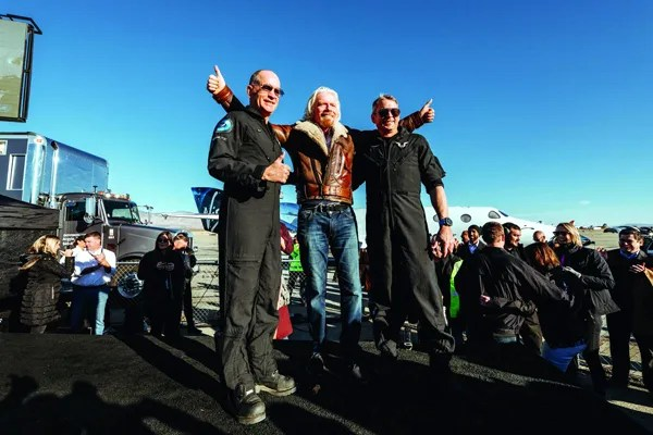 Sir Richard Branson poses with SpaceShipTwo pilots Mark 'Forger' Stucky and Frederick 'CJ' Sturckow after the VSS Unity safely returned to the Mojave Air & Space Port after her first powered flight to the edge of space...on December 13, 2018.