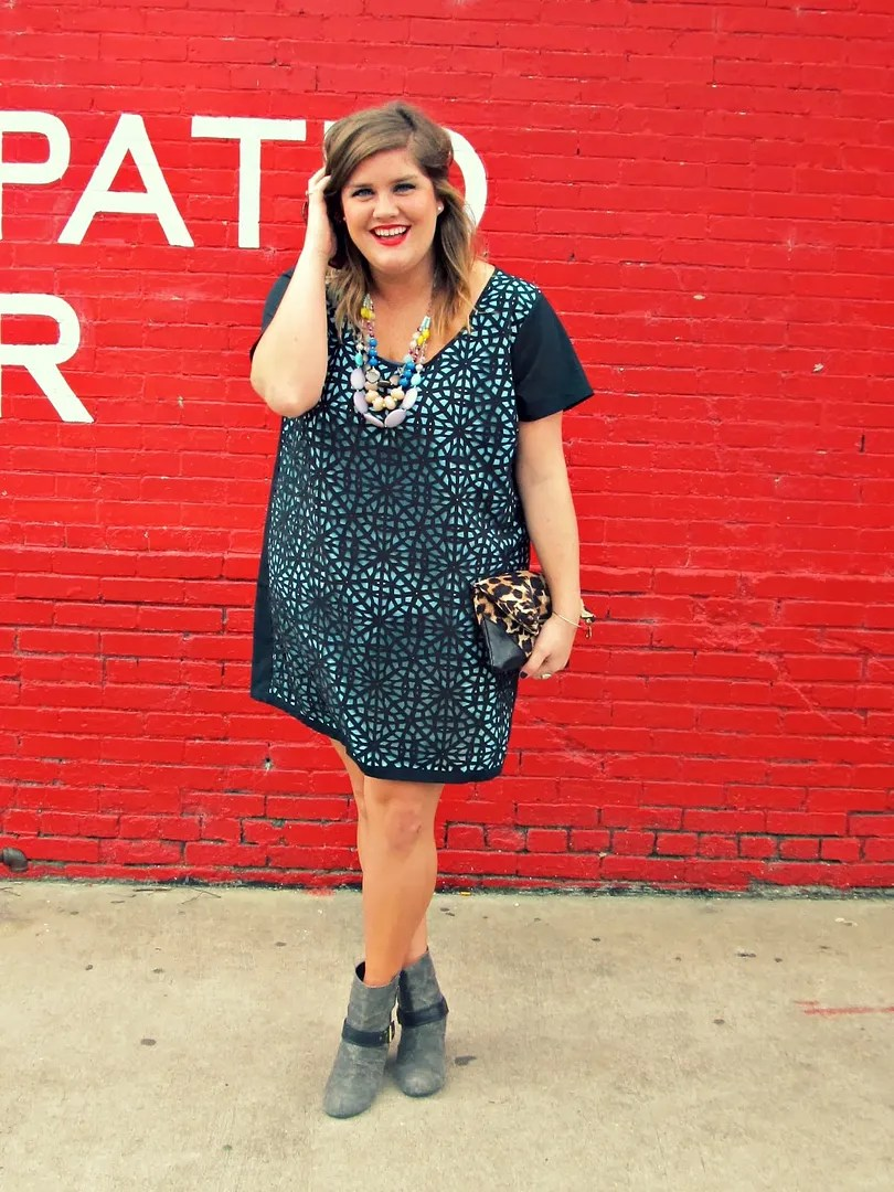 plus size outfit with laser cut blue and black dress and chunky necklaces
