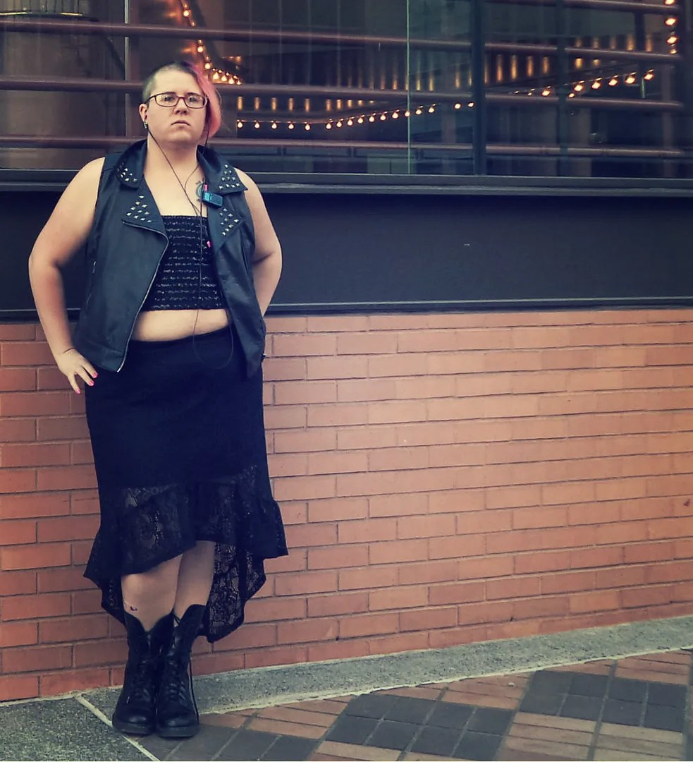 plus size hard femme outfit with leather vest and lace skirt and pink hair