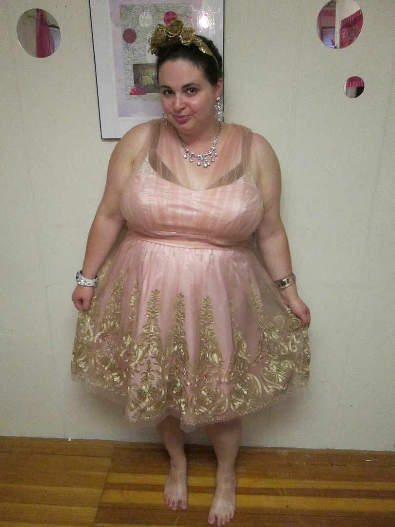 plus size woman wearing pale pink tulle dress with gold embroidery