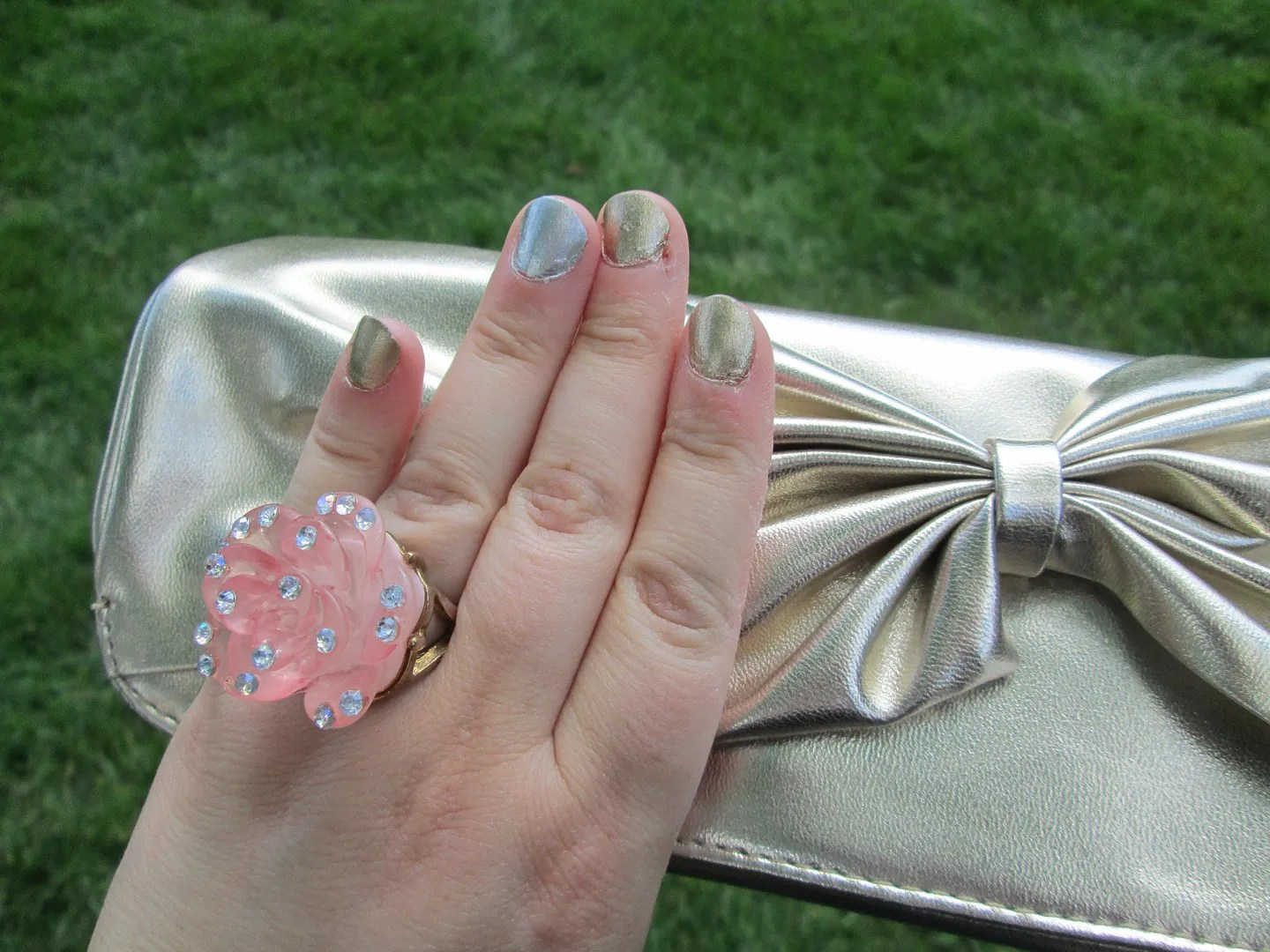close-up of hand with gold and silver nail polish and pink rose ring over gold clutch with bow