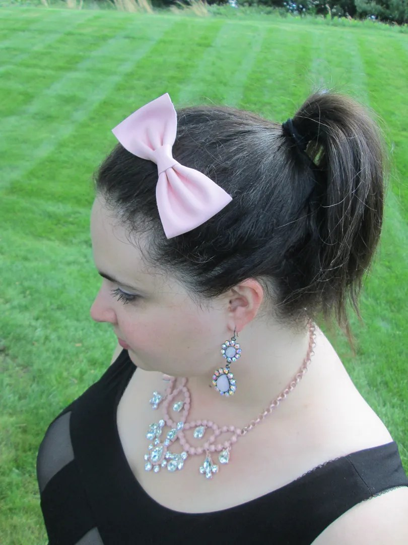headshot of glam pink, black, and beige outfit with pink leather hairbow