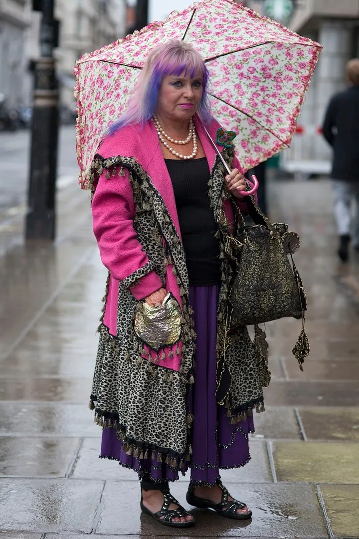 older woman wearing pink, purple, and leopard outfit with pink rose umbrella