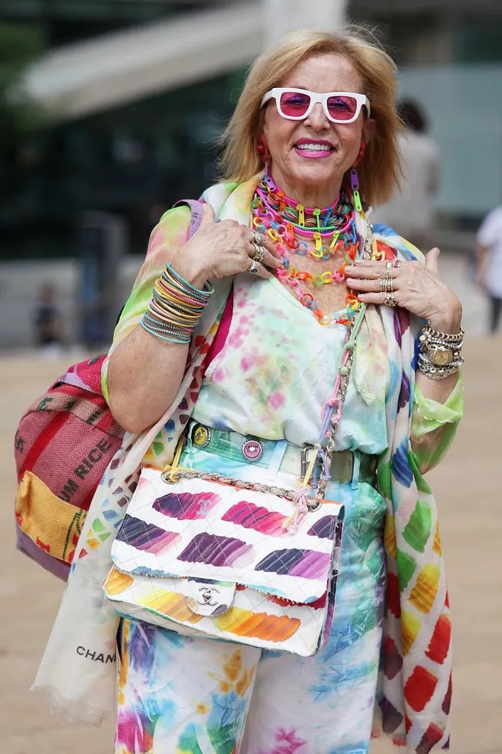 advanced style outfit with rainbow coat and purse and bright neon paper clip jewelry
