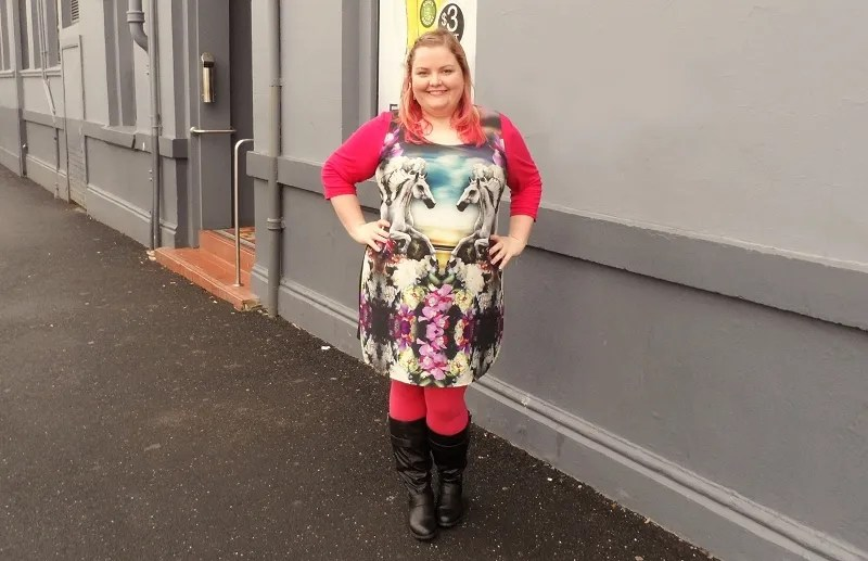 plus size woman wearing dress with fantasy horse print, red sleeves, and red tights with black boots