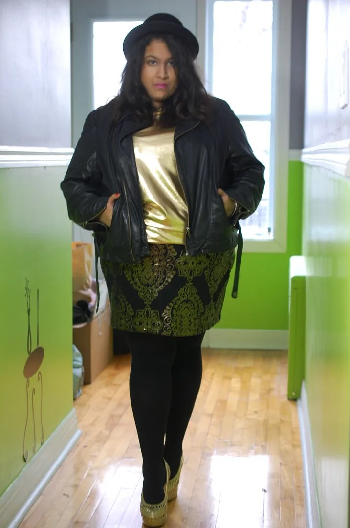 plus size woman wearing gold metallic top, leather jacket, and black and gold damask skirt