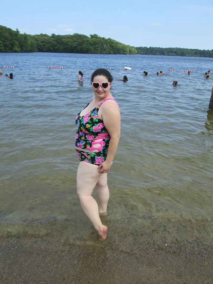 plus size woman wearing two piece black floral swimsuit standing in lake