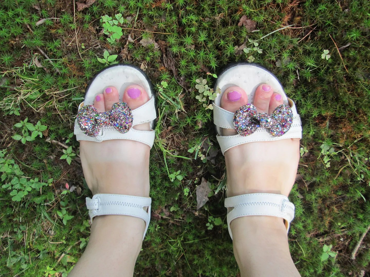 white sandals with glitter bows, pink nail polish