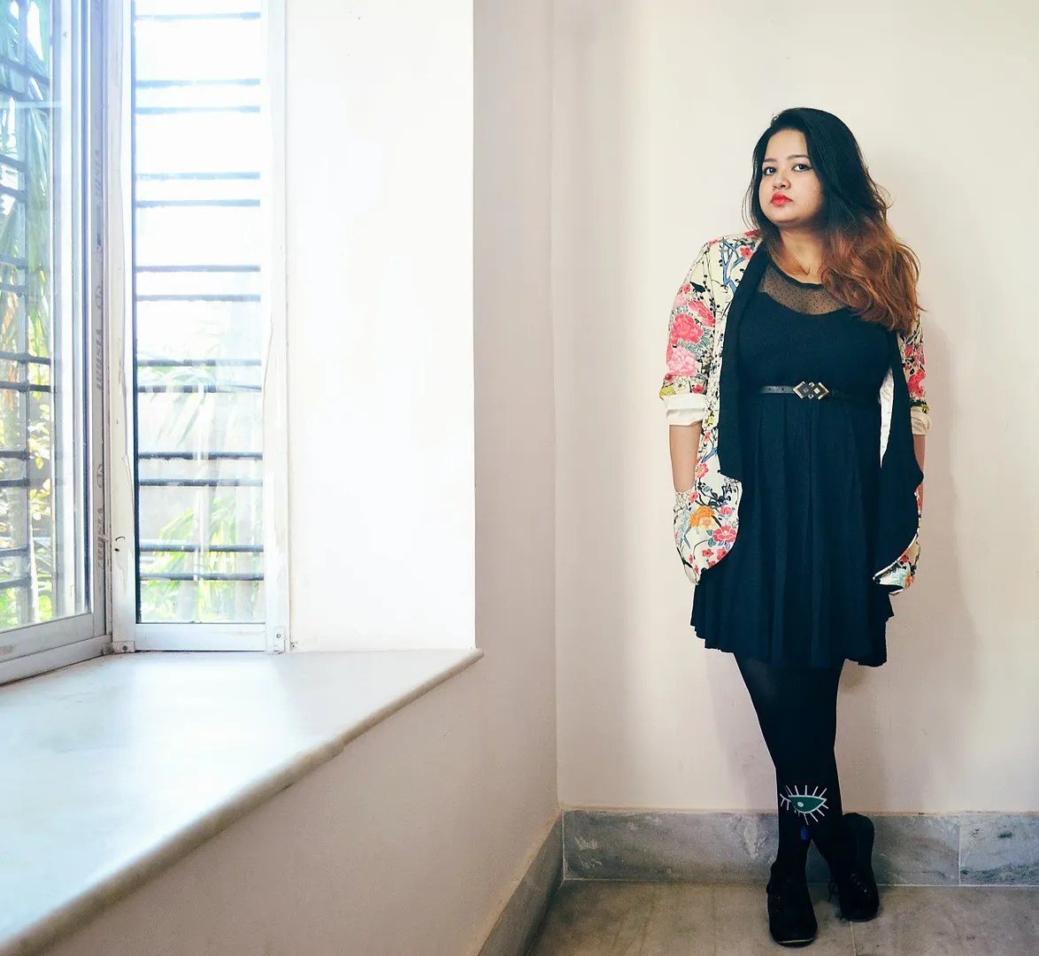 plus size outfit with black dress, floral jacket, and black tights with blue eye designs
