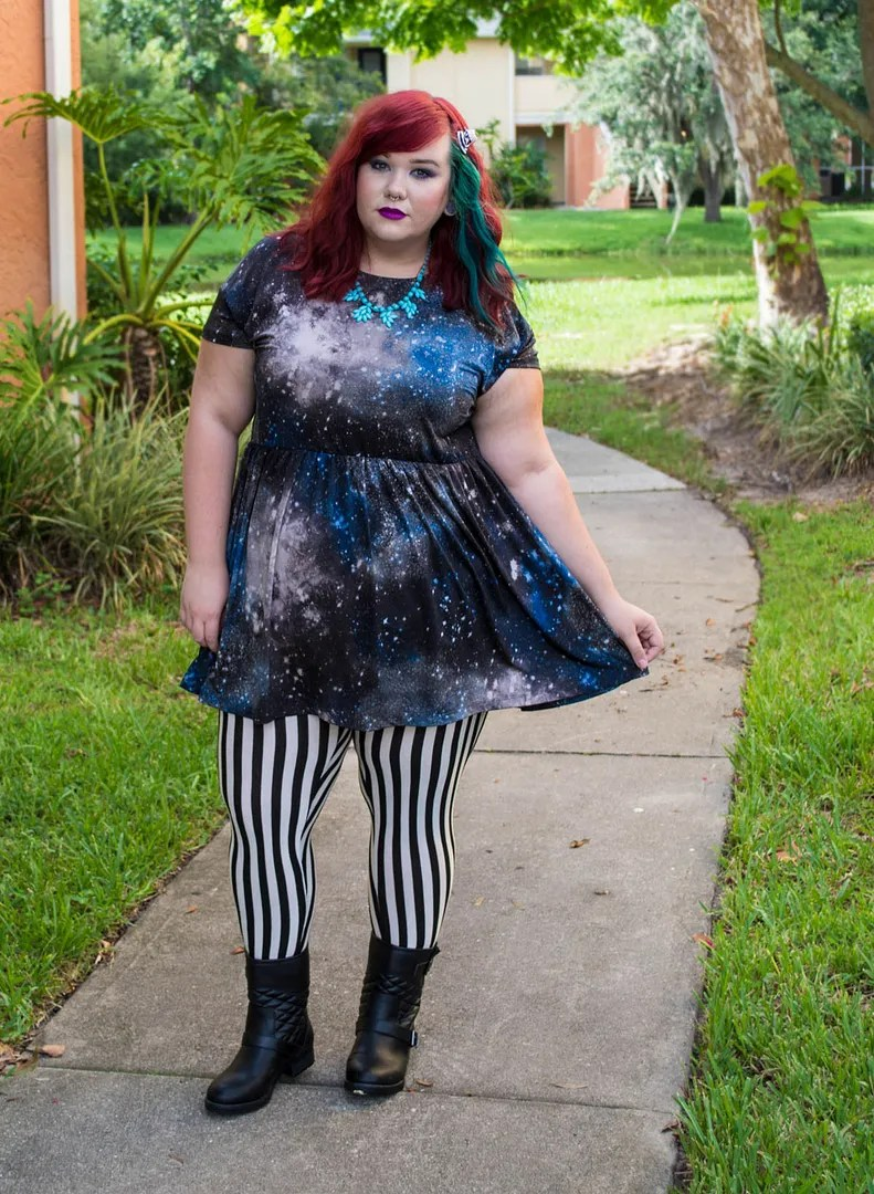 plus size outfit with galaxy print dress and black and white striped leggings