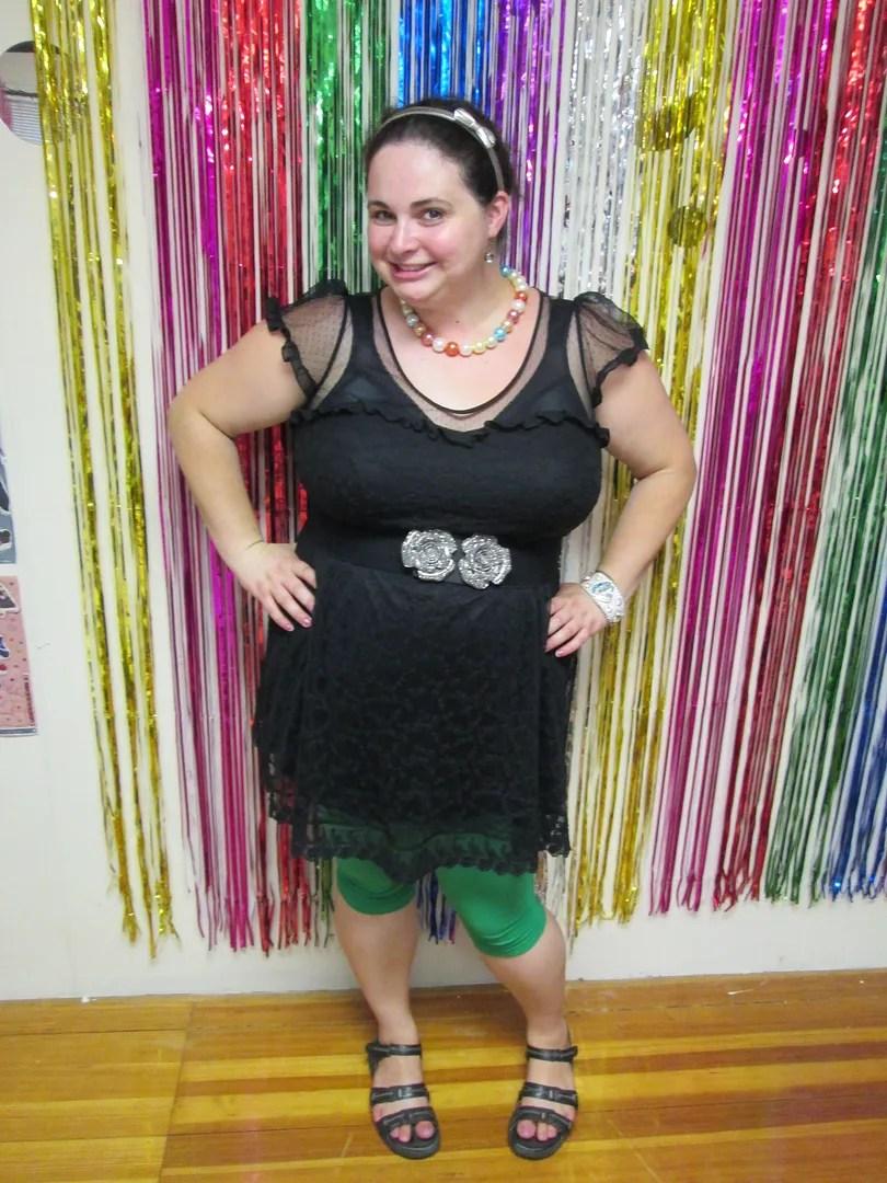 plus size outfit black dress, green leggings, multicolor pearl necklace, flower belt