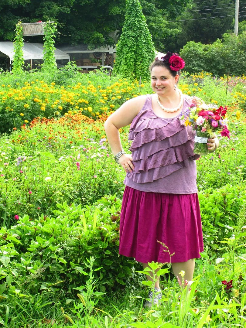 plus size purple and burgundy outfit with flower crown in flower field